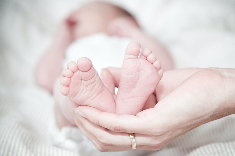 mom holding baby feet