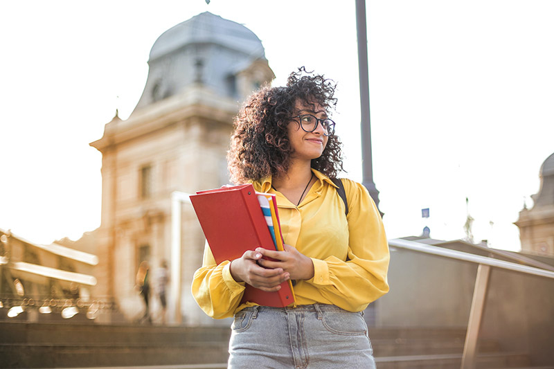 girl with yellow shirt holding school books in front of building