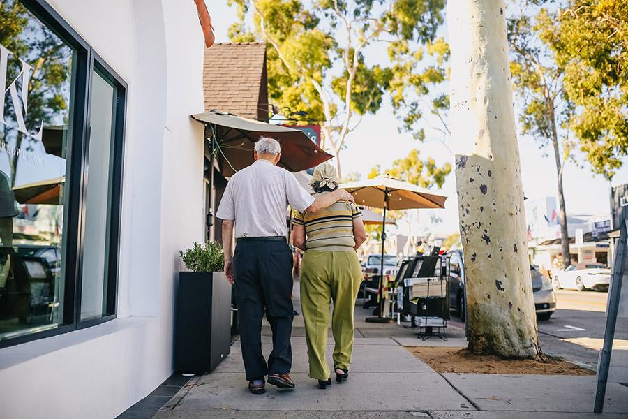 elderly couple walking down sidewalk