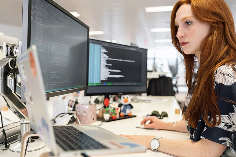 red haired woman working in front of a computer