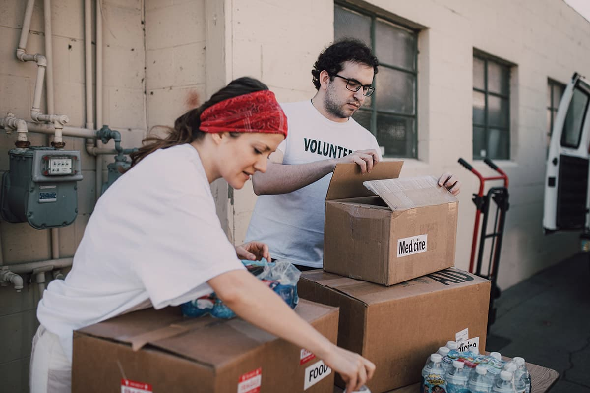 man and woman sorting boxes as volunteers